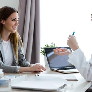 Patiente assise devant une professionnelle de la santé. Sur le bureau se trouvent des pots de médicaments, des documents, un ordinateur et un altère.