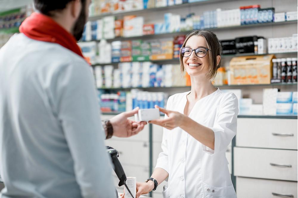 Pharmacienne sourit à un homme et lui tend une boite de médicaments