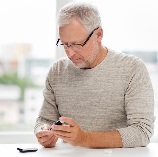 Homme dans la soixantaine assis à une table et mesurant sa glycémie.