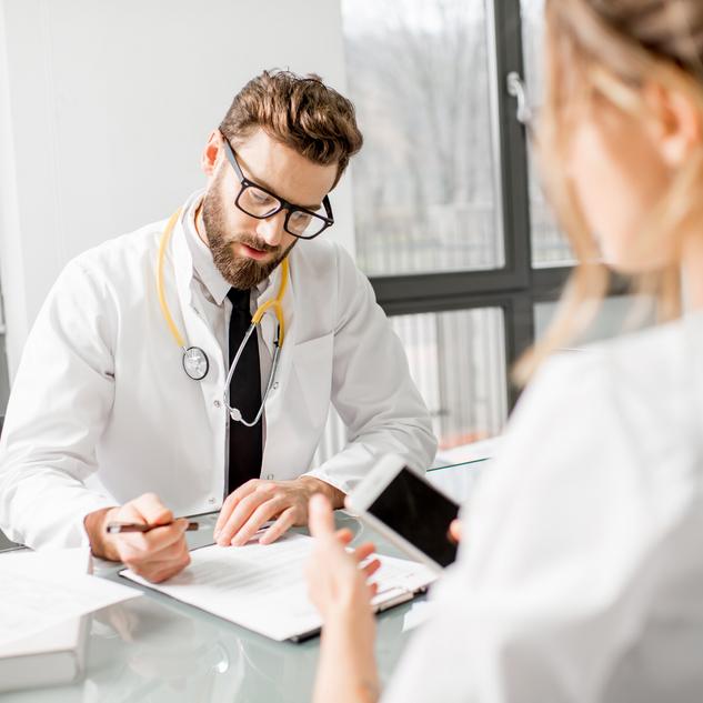 Professionnel de la santé révisant un document, sa patiente assise devant lui