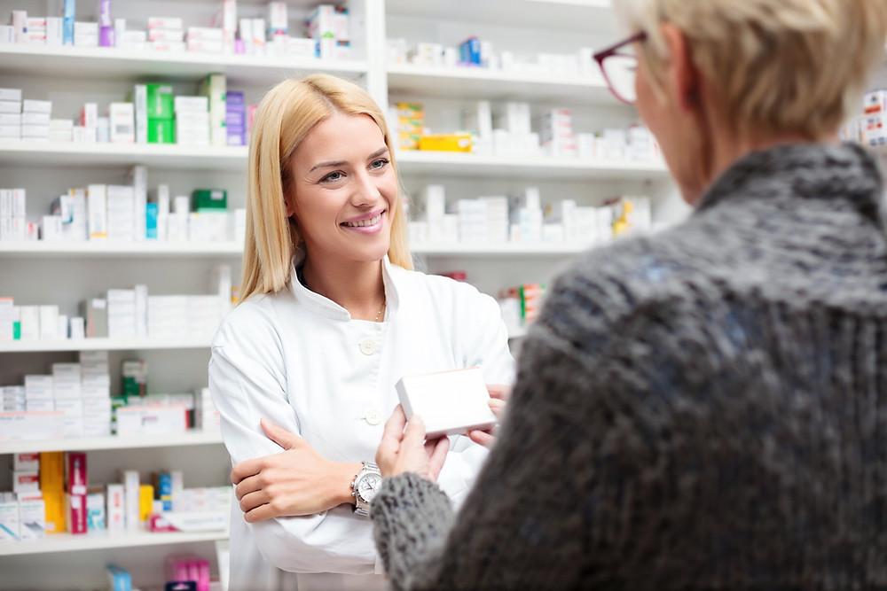 Pharmacienne sourit en regardant une cliente qui tient une boite de médicaments
