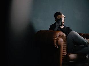 Homme assis dans un fauteil, se tenant le front d'une main