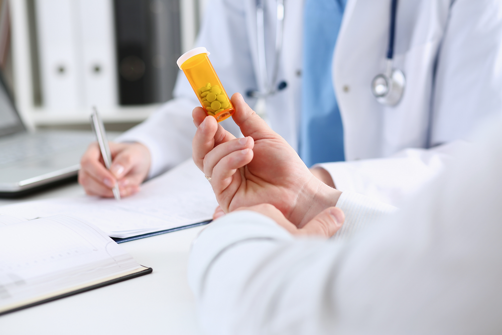 Mains tenant un flacon de pilules. Derrière, une personne en sarrau et portant un stéthoscope écrit sur des formulaires