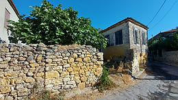 A traditional stone house with a large yard is for sale near Eressos square