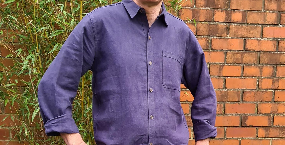 man standing in front of bamboo wearing dark mauve collared long sleeved shirt with buttoned front