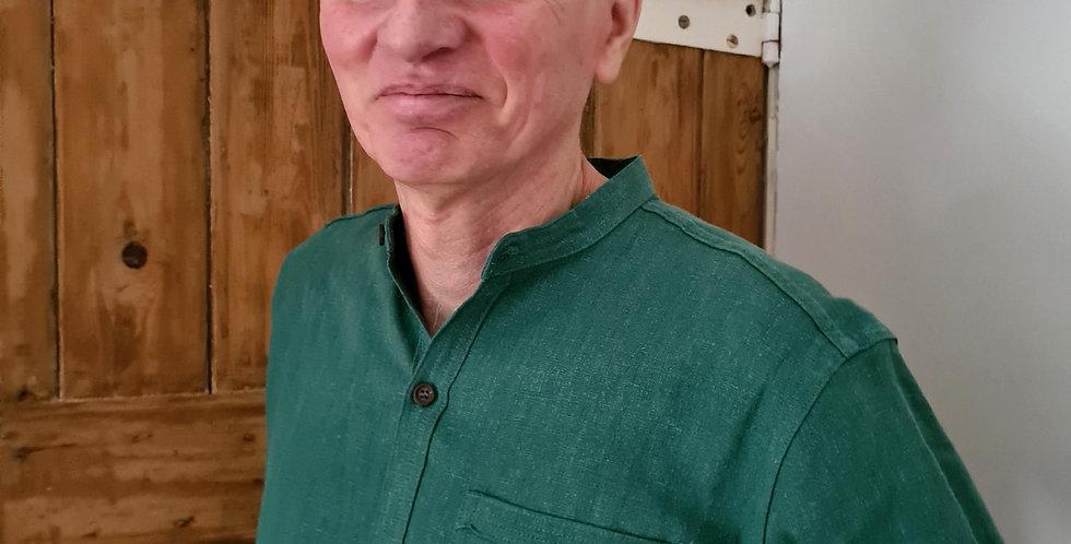 men in jungle green shirt with standing collar in front of wooden door