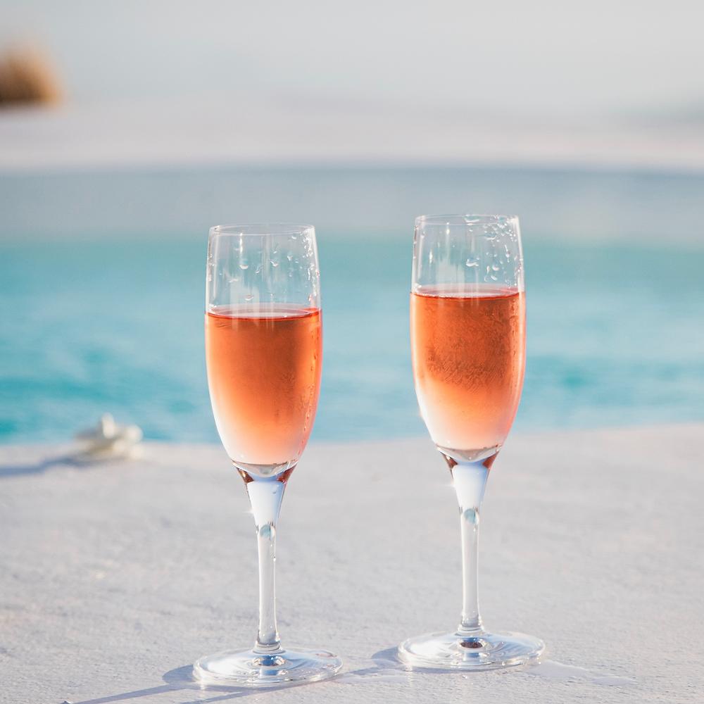 Deux flûtes de rosé avec la mer en arrière plan