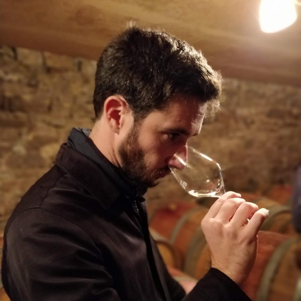 Dans une cave, Florian porte le verre à son nez pour sentir le vin blanc