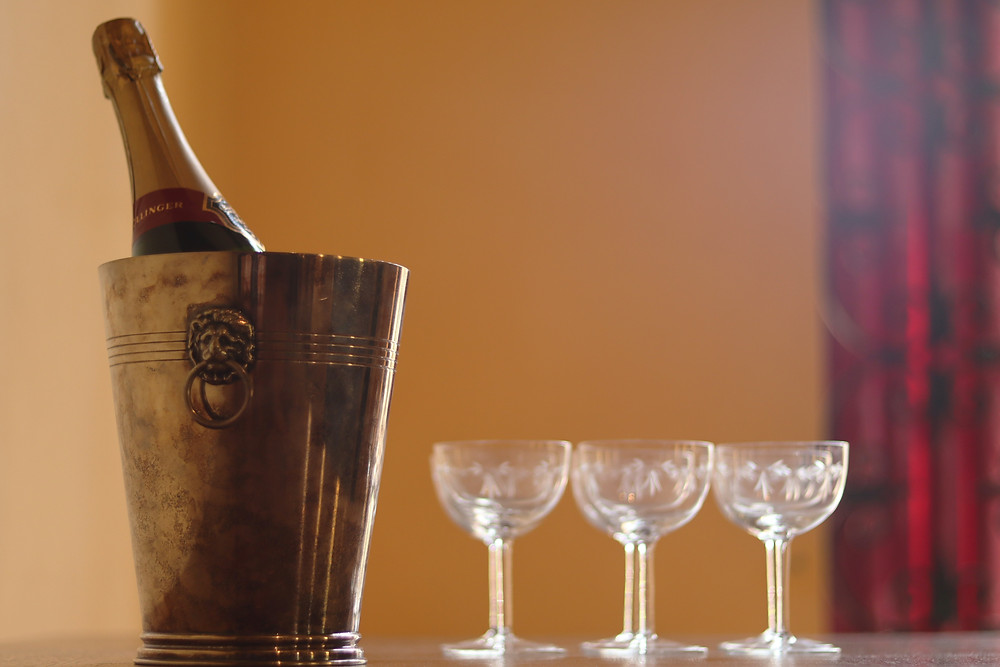 Bouteille de champagne dans un seau avec trois verres vides