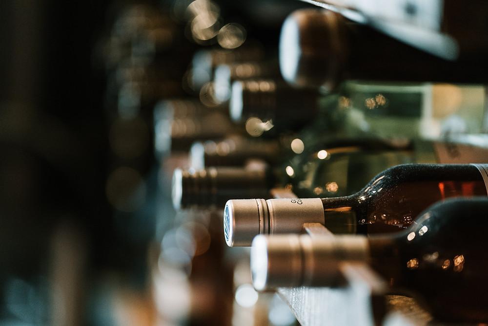Plusieurs bouteilles alignées sur une étagère de cave à vin