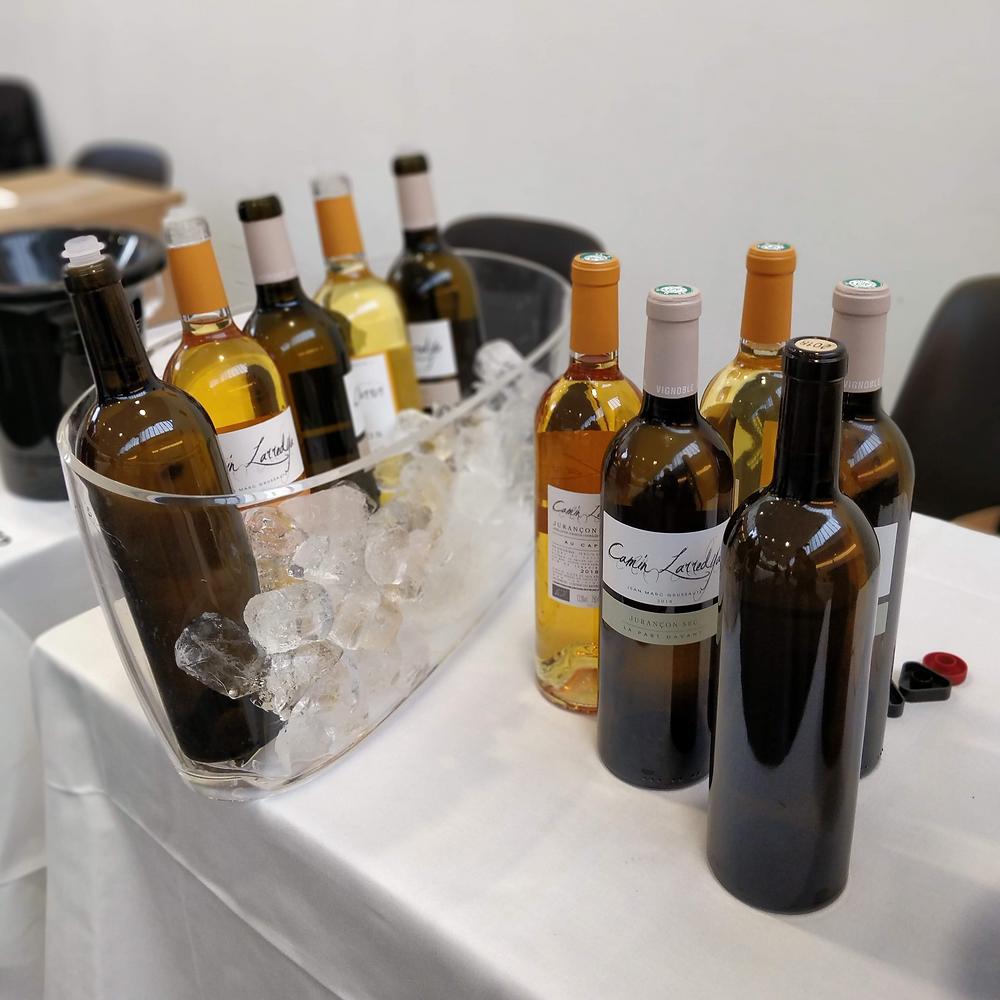 10 bouteilles de vins blanc sur une table prêtes à la dégustation