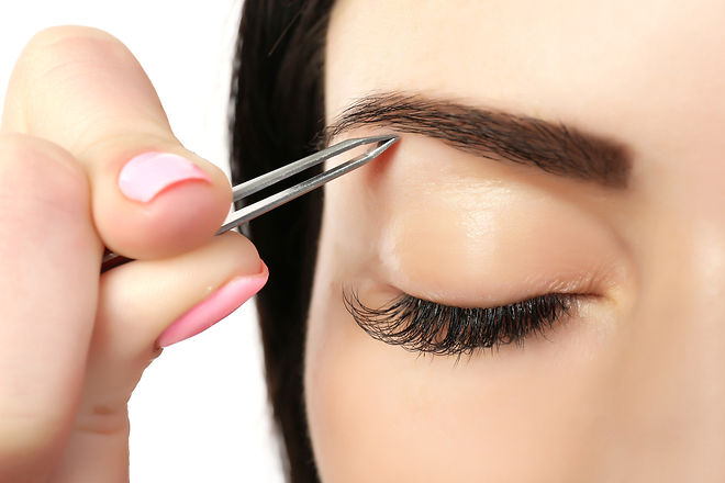 Young woman plucking eyebrows with tweezers close up.jpg