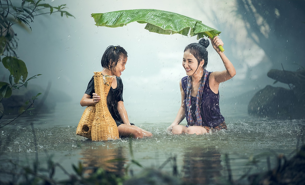Woman and daughter under large leaf to protect themselves from the rain.