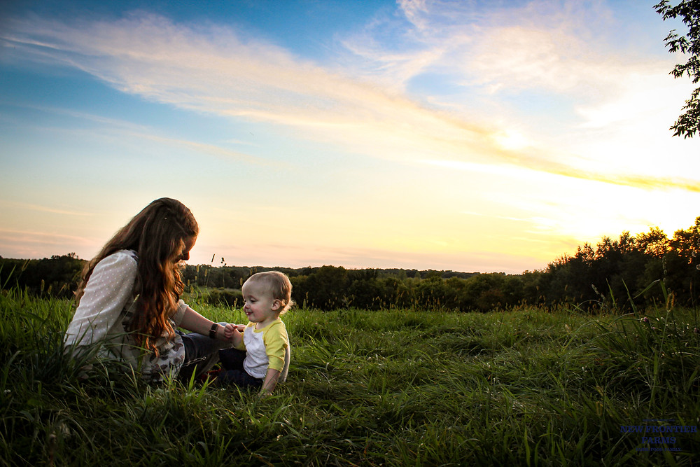 mother and child sitting in field with sunset in background