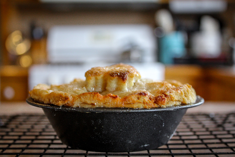 fresh homemade apple pie on a cooling rack in front of an oven
