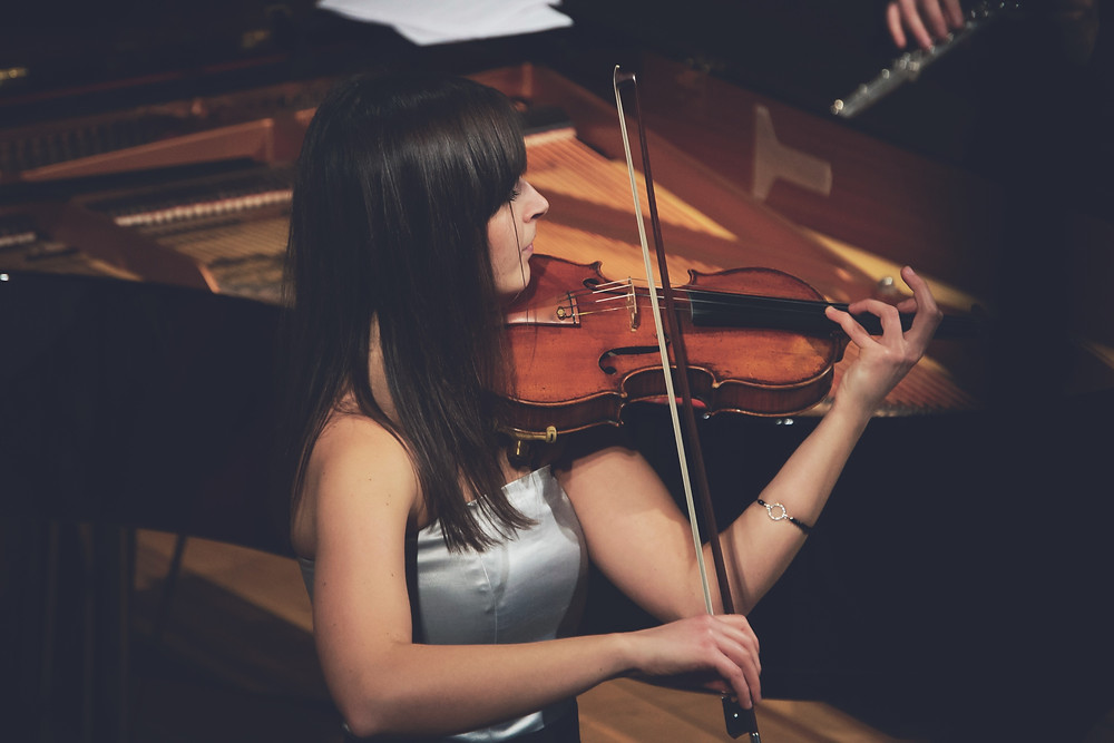 Woman playing violin in concert hall
