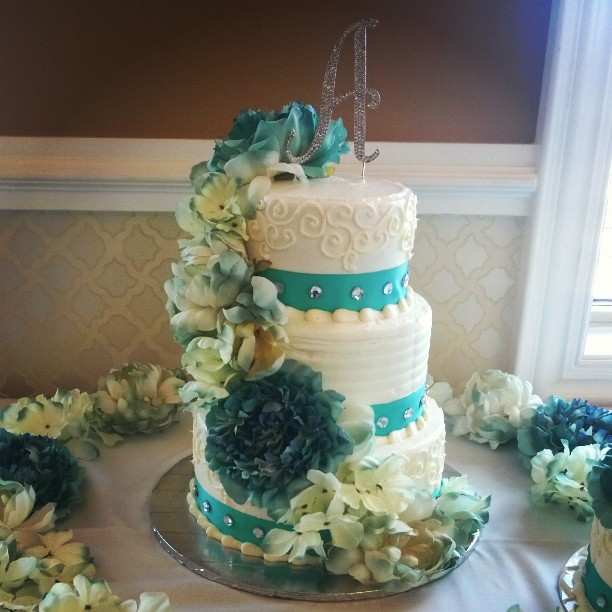 3 tiered Teal wedding cake with cascading flowers