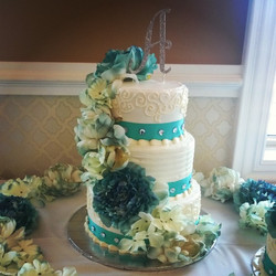 3 tiered Teal wedding cake with cascading flowers. Www.specialtysweetc