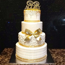 4 tier gold and white buttercream iced wedding cake