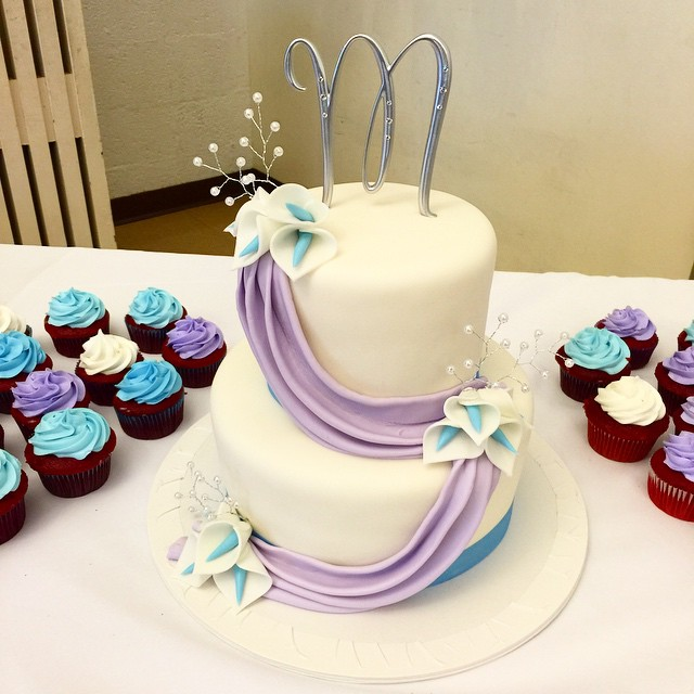 Two tiered fondant draped wedding cake and matching cupcakes.