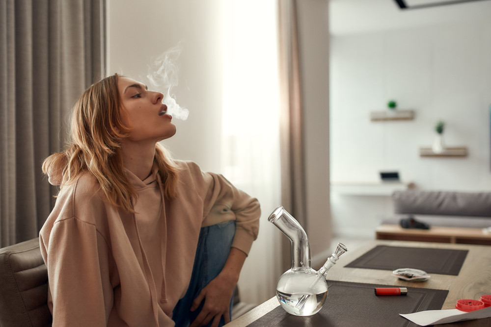 Young caucasian woman exhaling the smoke while smoking marijuana from a bong or glass water pipe, sitting in the kitchen