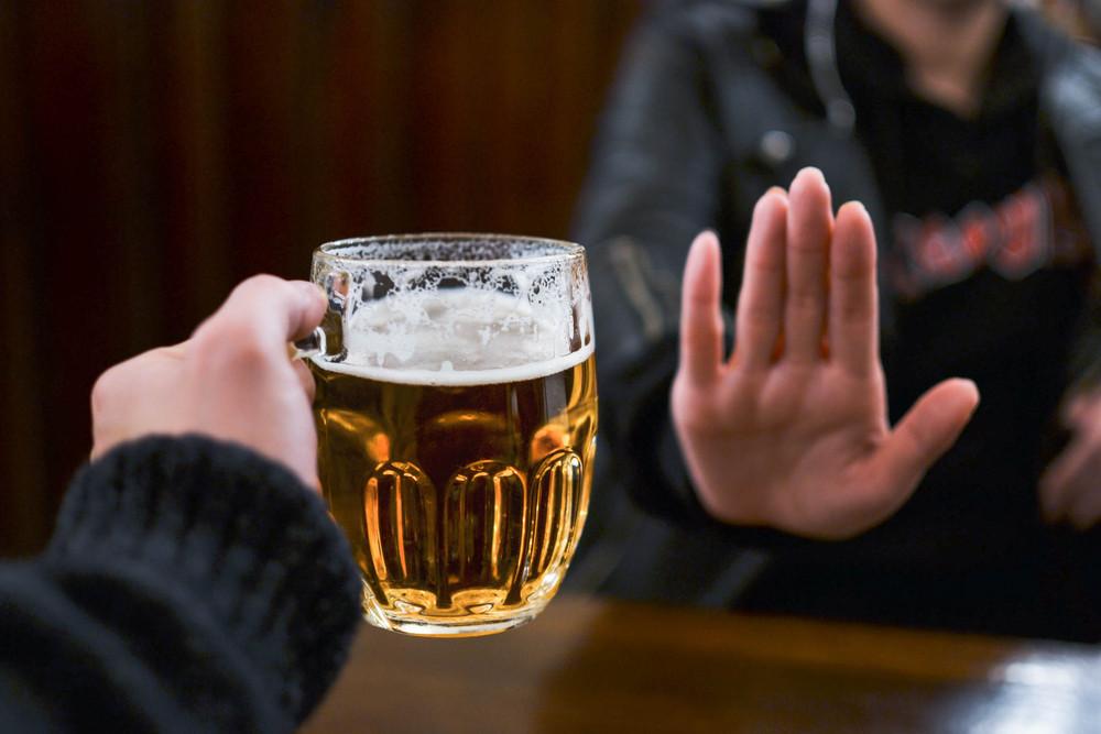 female hand turning down a mug of beer