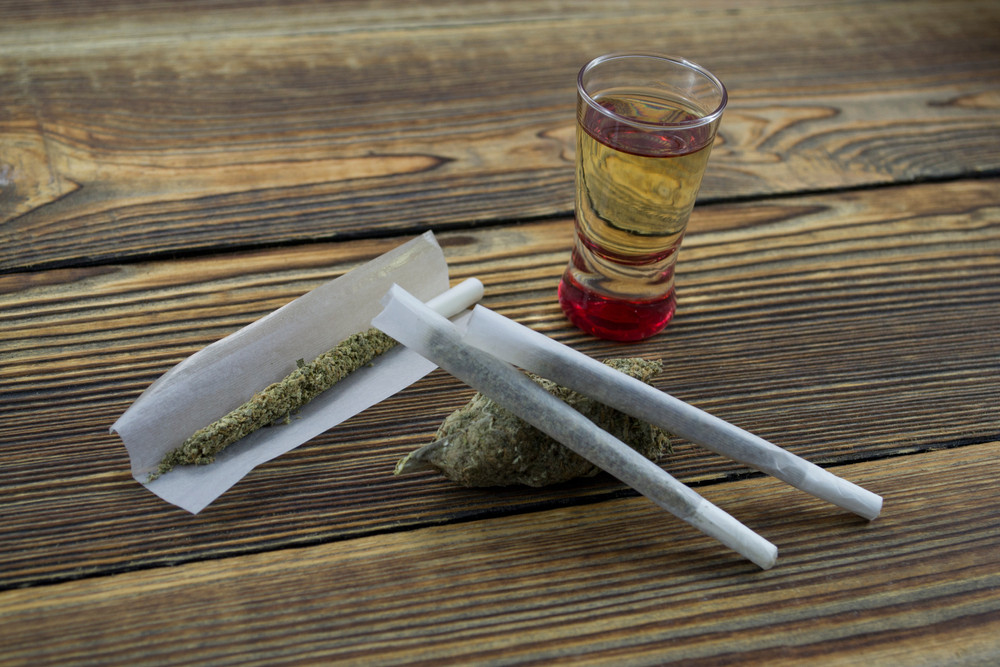 Joint, grinder, cannabis buds, alcohol shot and related items on a table