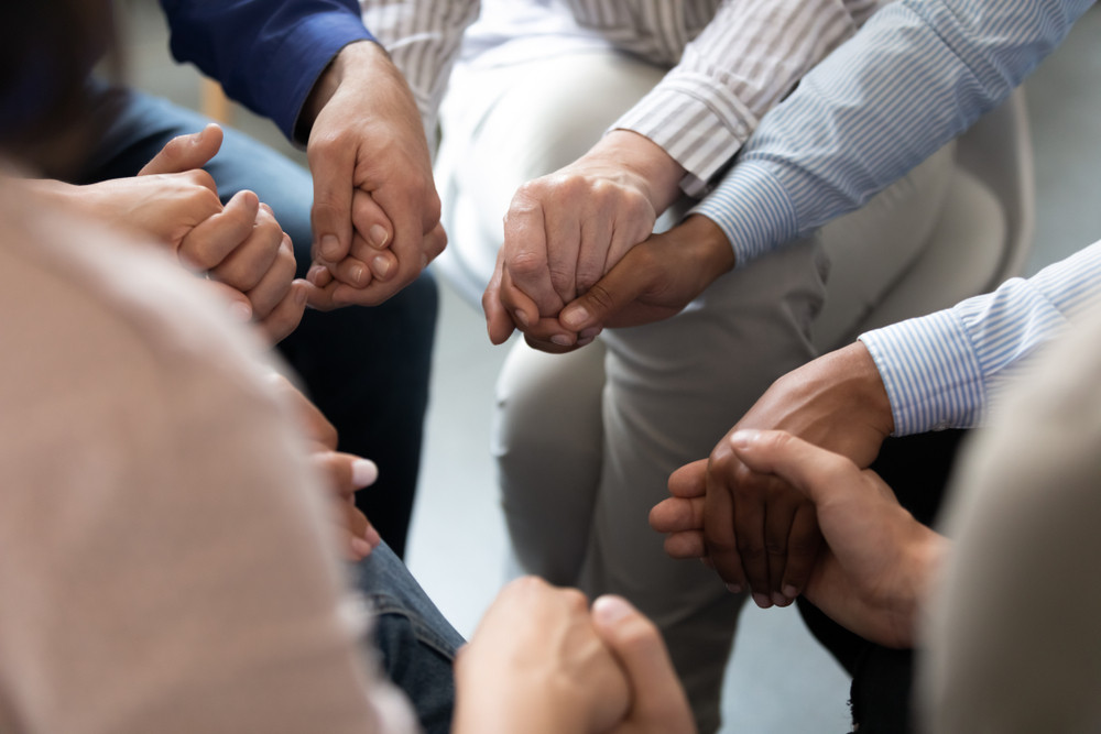 Close up people sit in circle holding hands participating at group therapy session