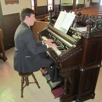 Justin-playing-antique-reed-organ.jpg