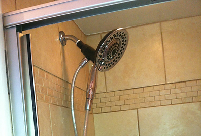 New Delta shower head and custom tile work on a new shower pan in bathroom remodel by BEEZ Construction