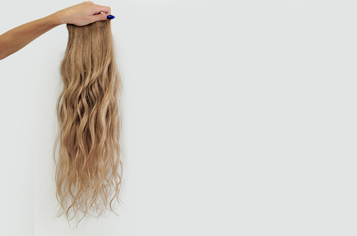 Female hand holding wavy blonde wig on a
