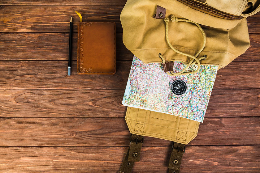 backpack-map-and-compass-on-wooden-backg