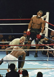 A bruised Mike Tyson watches Douglas get to his feet at the end of round 8