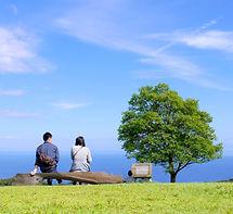 夫婦が草原から海を見ている写真