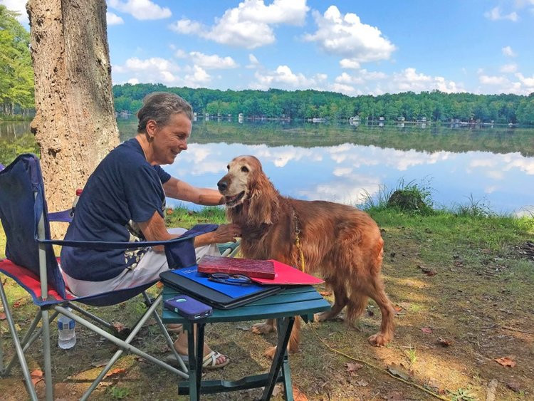 Author Pati Redmon sitting next to lake with dog