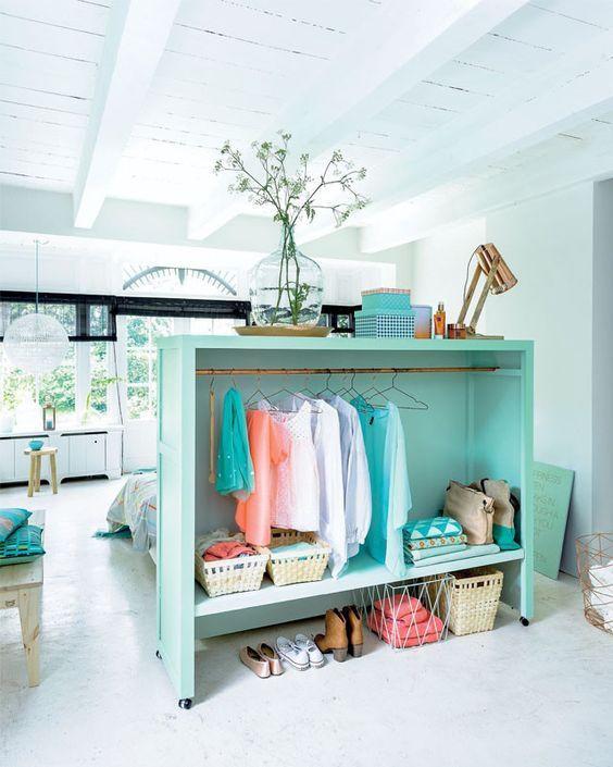 Arara de roupas/closet dividindo os ambientes integrados.
