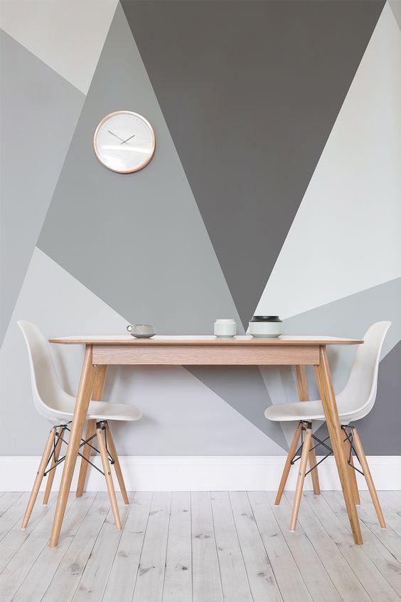 Pintura geométrica na parede em tons de cinza.