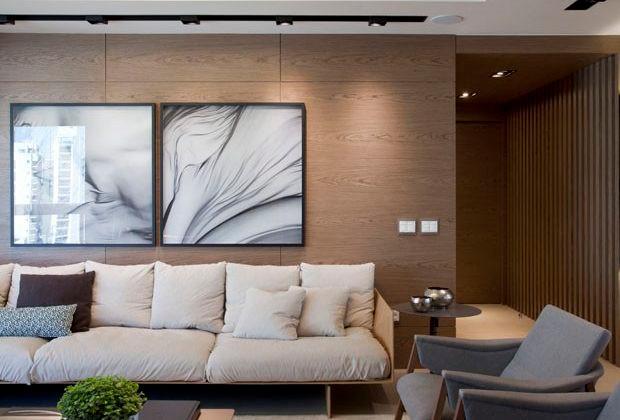Sala de estar contemporânea com painel em madeira.