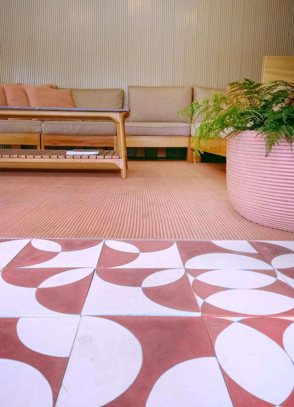 Sala de estar rosa com ladrilho hidráulico.