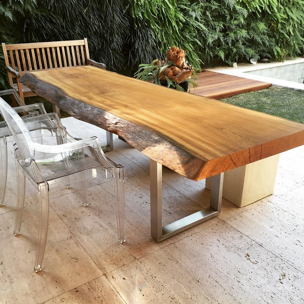 A união dos elementos rústicos aos contemporâneos: mesa em madeira pequiá com pés metalizados e mobiliário em acrílico.