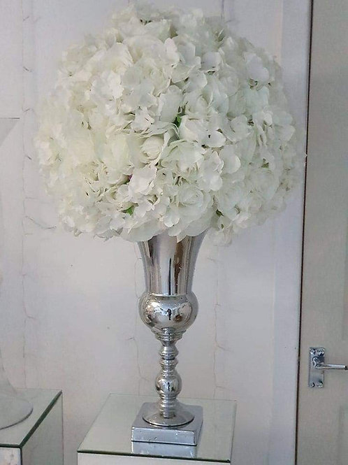 Silver urn vases with flower topper on mirror table plinth
