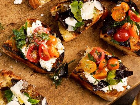 Boquitas de pan tostado, queso de cabra y tomates