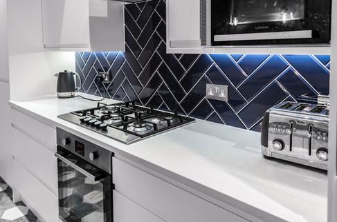 Modern kitchen, extension, blue tile, white doors, corian surfaces, industrial lighting, rooflights, modernist