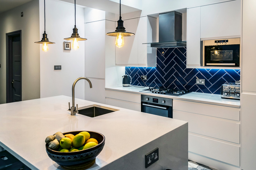 Modern kitchen, extension, blue tile, white doors, corian surfaces, industrial lighting, rooflights, modernist