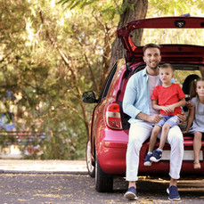 Family with kids sitting in car trunk.jp