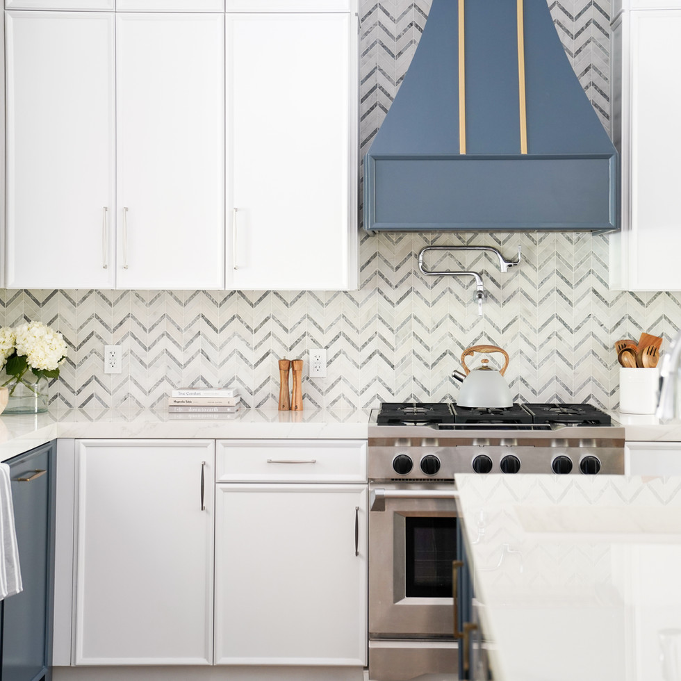 Transitional white kitchen with custom blue decorative hood