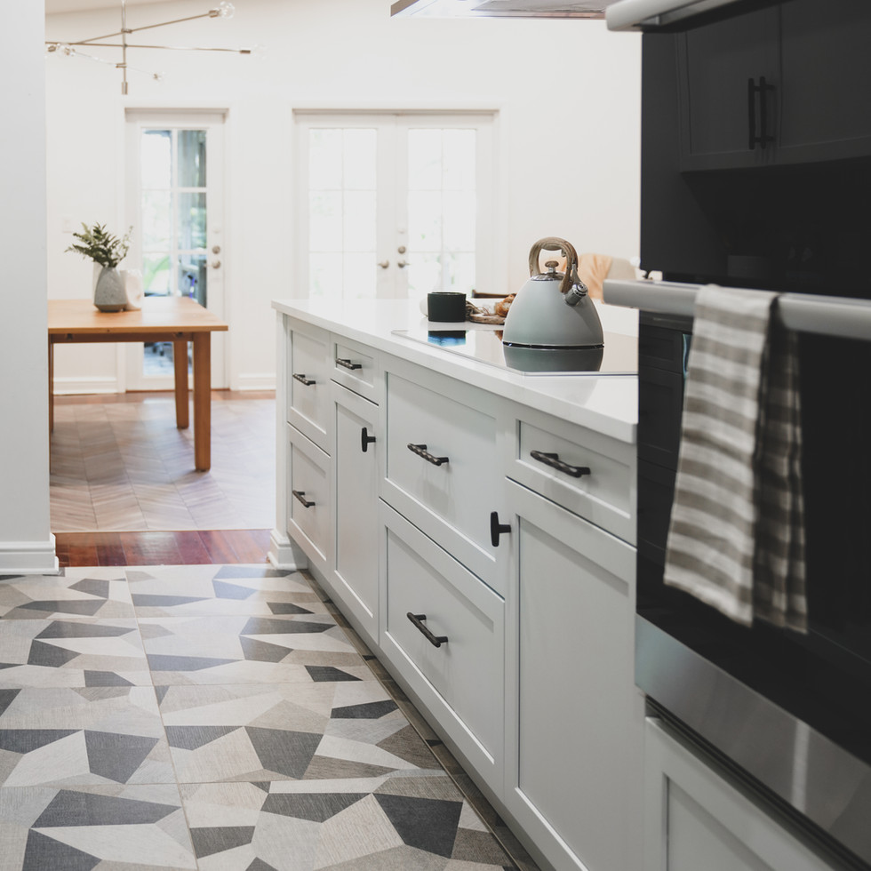 Bright, white and airy galley kitchen in Coconut Grove, FL showcases bold patterned flooring and a Ann Sacks backsplash