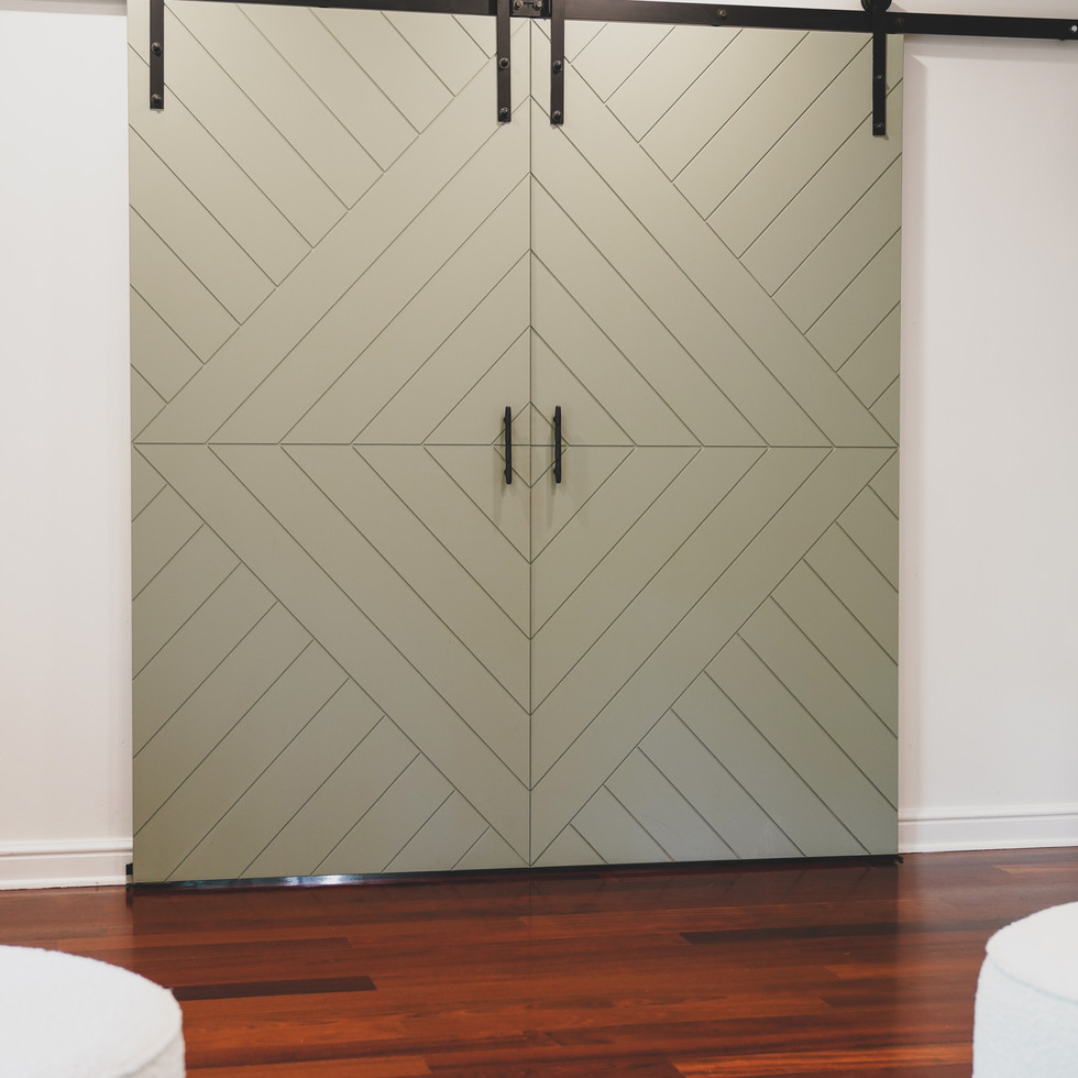 Sage Green Barn Doors with a Geometric pattern and black matte hardware