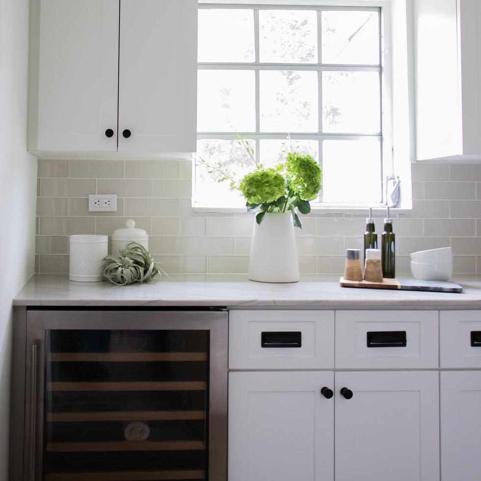 Modern bright white kitchen with wine cooler designed by Miami based interior design studio KJ Design Collective