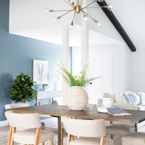 Dining room with a dark wood beams and blue accent wall that is complemented with modern furnishings